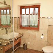 Badezimmer mit Dusche und WC, Wandspiegel und Fenster