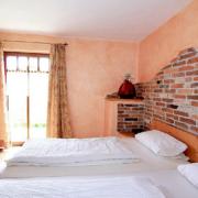 Schlafzimmer mit roter Wandfarbe, ein Doppelbett und ein Kleiderschrank