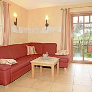 Wohnbereich mit roter Couch und Beistelltisch, eine Balkontüre zur Terrasse und ein Esstisch