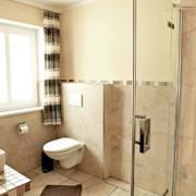 Badezimmer mit Fenster, WC, Glasduschkabine und Waschbecken