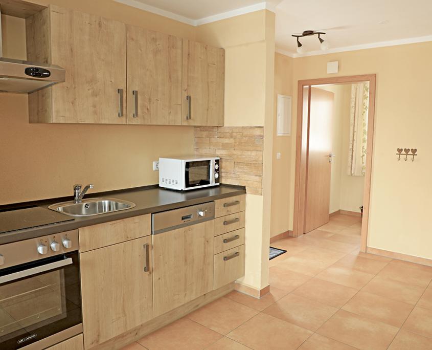 Küche in Holzoptik,mit Microwelle, Spülmaschine, Herd mit Ceranfeld. Dusntabzug