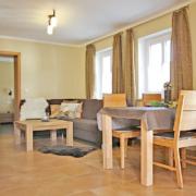Ein Raum mit Esstisch, Couch mit Couchtisch, gelber Wand und Fenster, SAT/TV